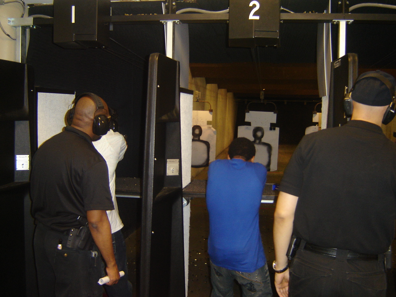 Instructors Leon S. Adams and Joseph Hibner give pointers to new shooters on the firing line