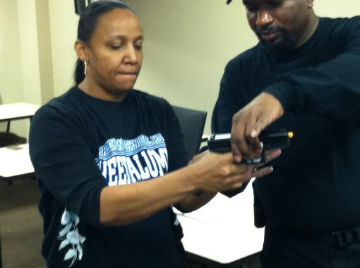 Instructor Leon S. Adams instructs a first time student on basic handgun fundamentals during Introduction to Handguns for Self Defense